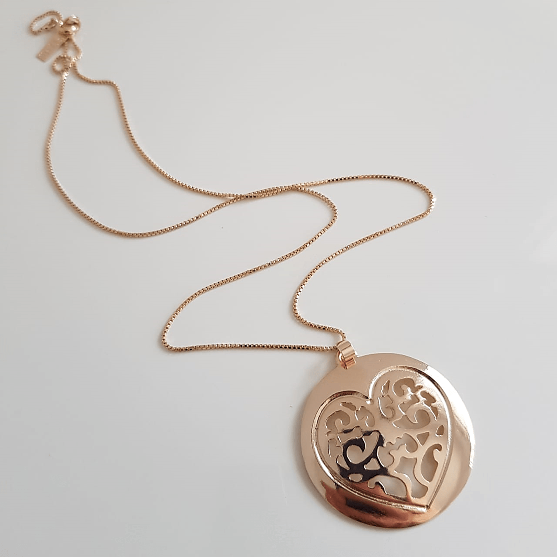 Colar curto com pingente medalha com desenho coração vazado