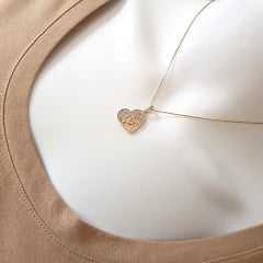 Colar dourado com pingente coração.